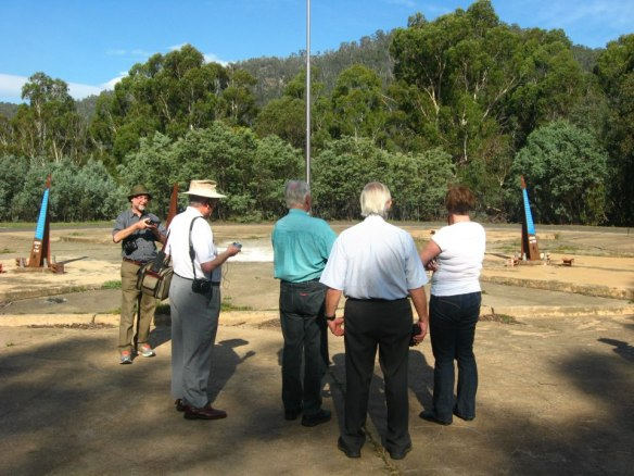 John Saxon (blue shirt) and Hamish Lindsay (white shirt, grey hair) show us around their old work place at the Honeysuckle Creek site - now a historic monument of markers and building slabs.