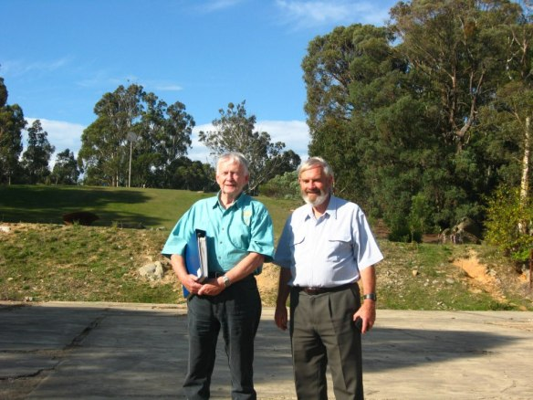 John Saxon (Honeysuckle Creek staff) and Hamish Lindsay (Honeysuckle Creek staff) stand at what was one the front door - basement level. The building's first floor extended further back on the rise behind them with the antenna in the distance
