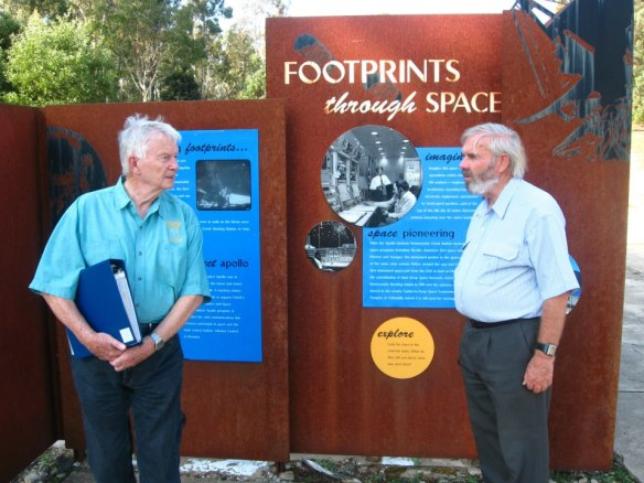 John Saxon (Honeysuckle Creek staff) and Hamish Lindsay (Honeysuckle Creek staff) stand in front of pictures showing the staff and operations of the site